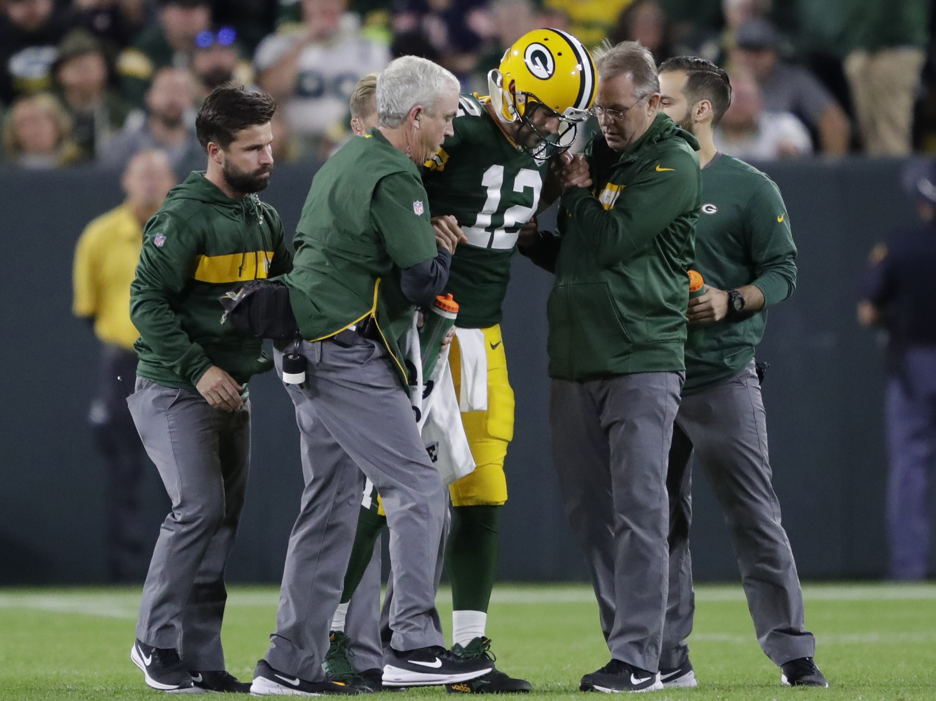 Green Bay Packers quarterback Aaron Rodgers (12) is helped off the field after getting injured during the second quarter against the Chicago Bears Sunday, Sept. 9, 2018, at Lambeau Field in Green Bay, Wis.