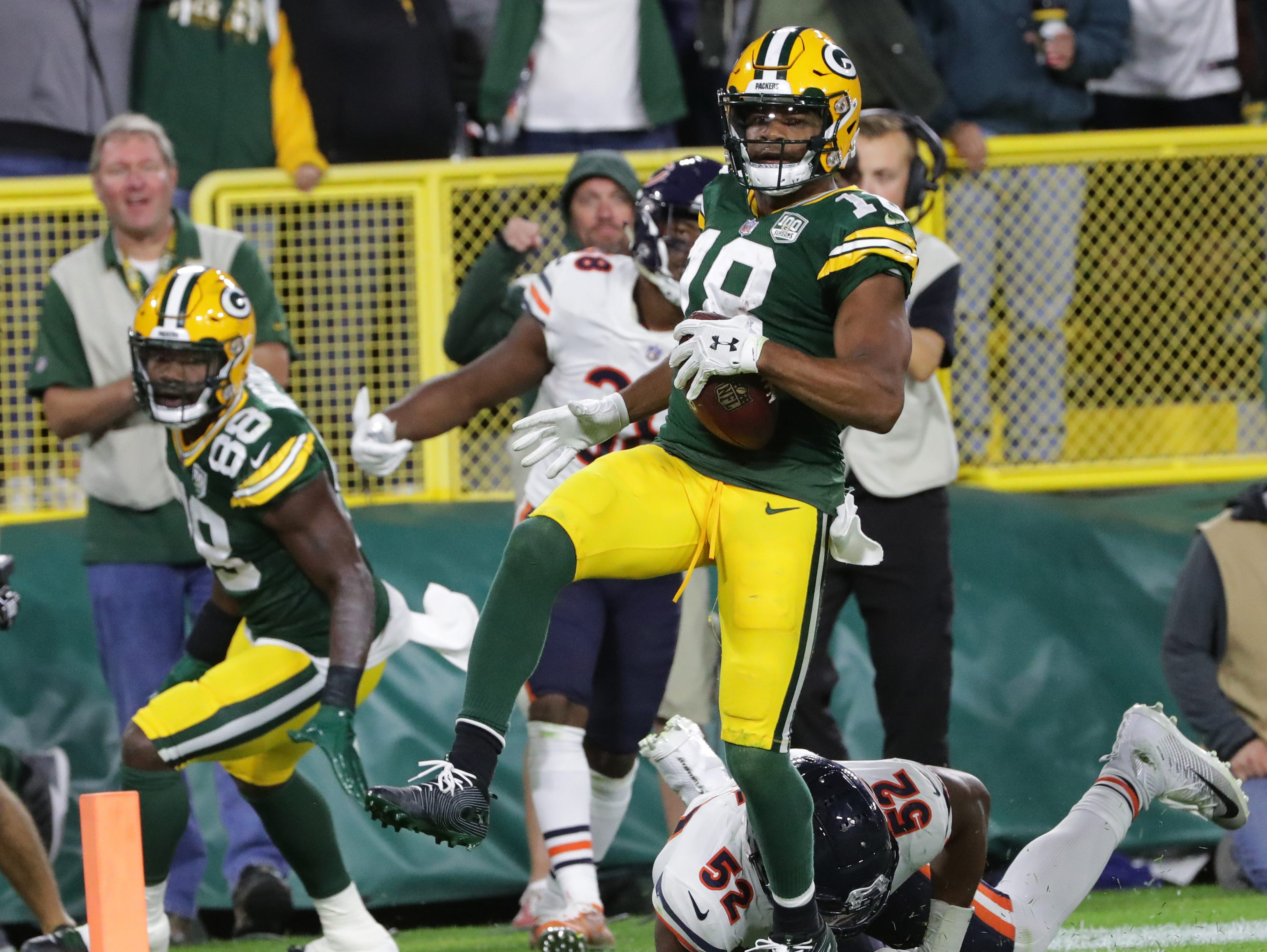 Green Bay Packers wide receiver Randall Cobb (18) scores a touchdown on a 75-yard reception despite the efforts of Chicago Bears linebacker Khalil Mack (52)during the fourth quarter of their game against the Chicago Bears Sunday, September 9, 2018 at Lambeau Field in Green Bay, Wis.