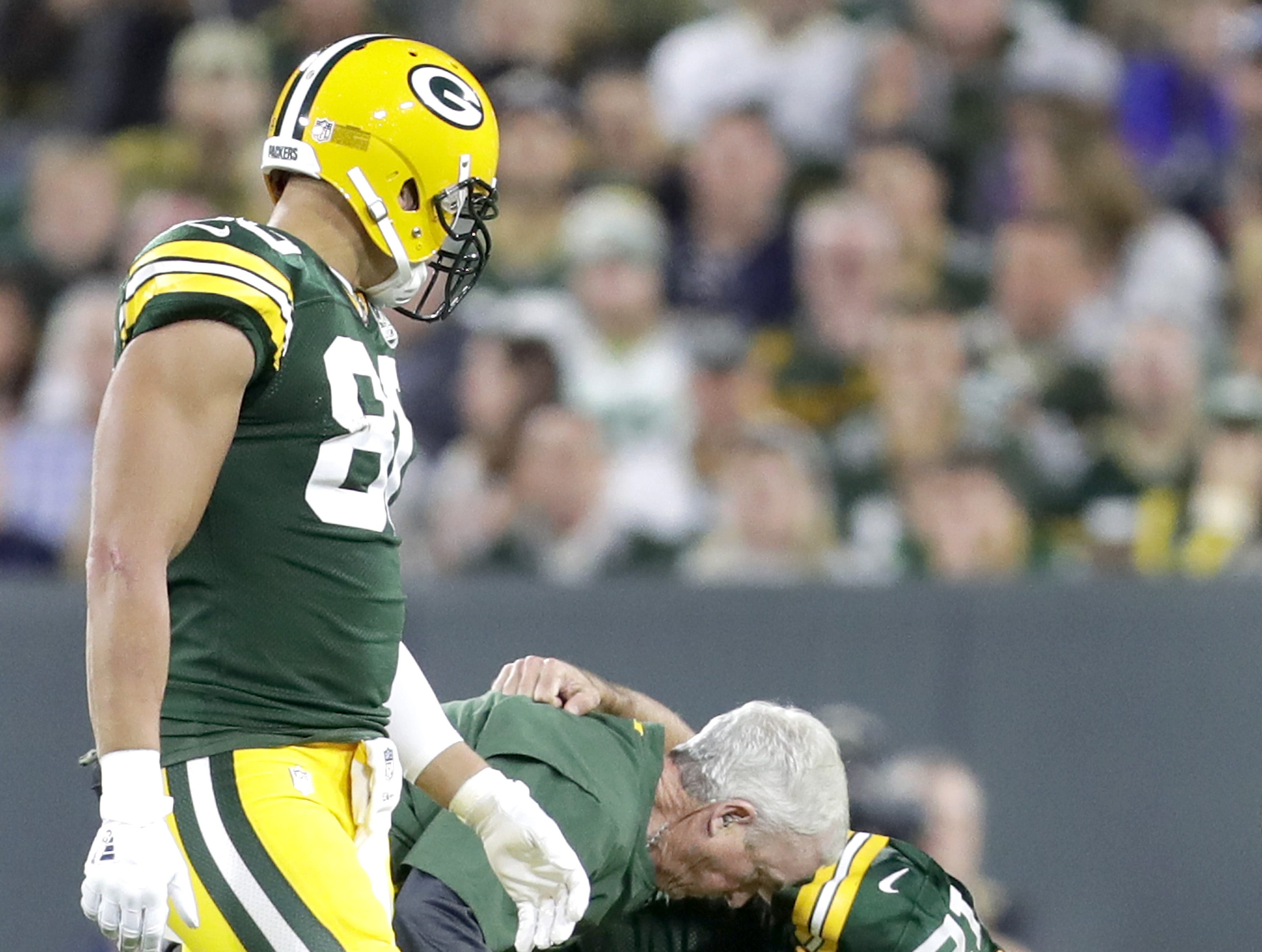 Green Bay Packers' Aaron Rodgers is helped to his feet aftyer being injured in the second quarter against the Chicago Bears in the season opener on Sunday, September 9, 2018, at Lambeau Field in Green Bay, Wis.