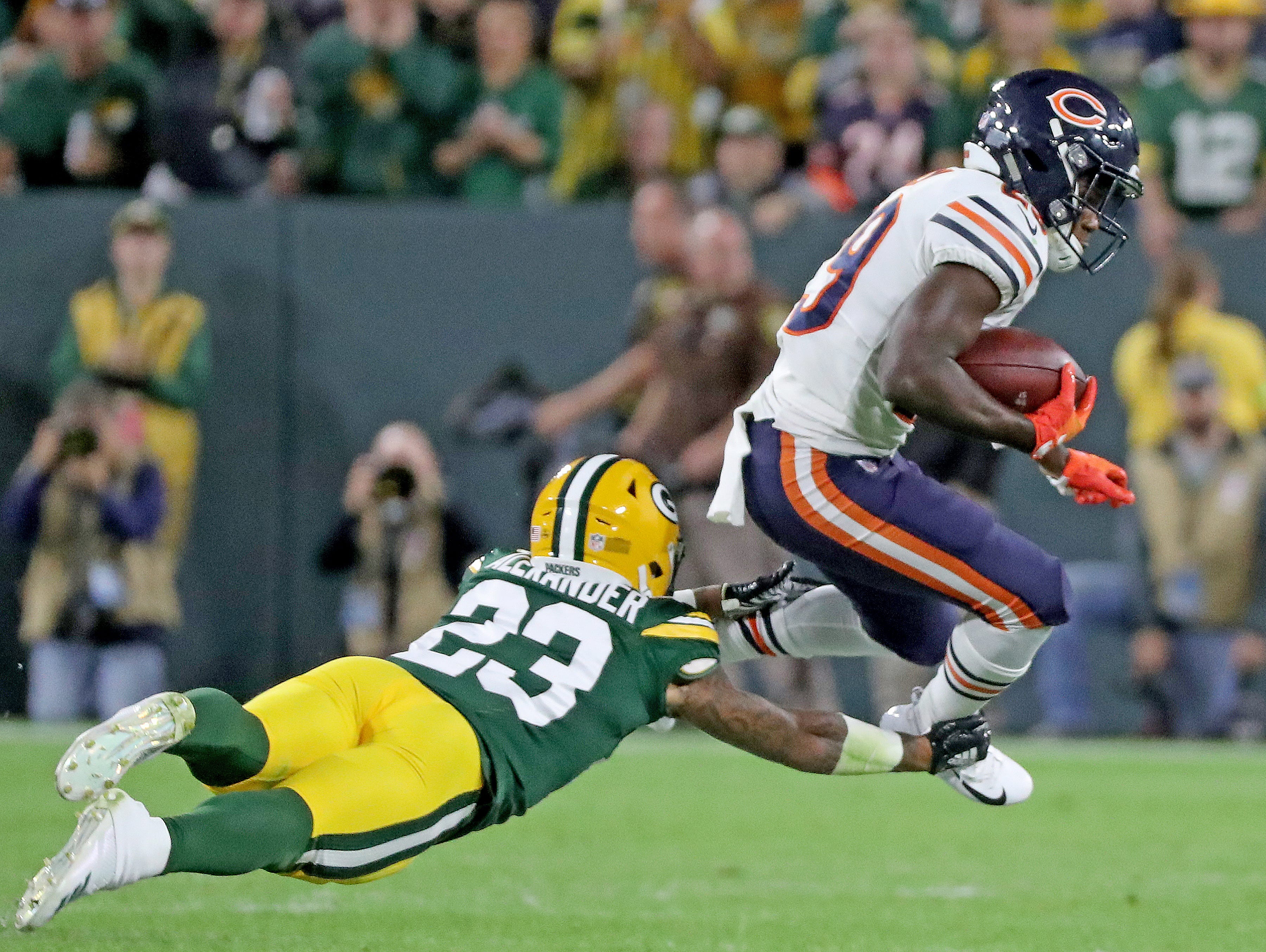 Green Bay Packers cornerback Jaire Alexander (23) dives at the feet of running back Tarik Cohen (29) against the Chicago Bears Sunday, September 9, 2018 at Lambeau Field in Green Bay, Wis.