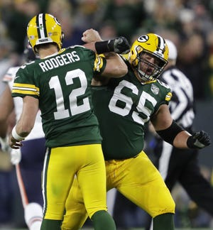 Green Bay Packers quarterback Aaron Rodgers (12) celebrates with Lane Taylor (65) after throwing a touchdown pass to Geronimo Allison (81) in the fourth quarter Sunday, Sept. 9, 2018, at Lambeau Field in Green Bay, Wis.