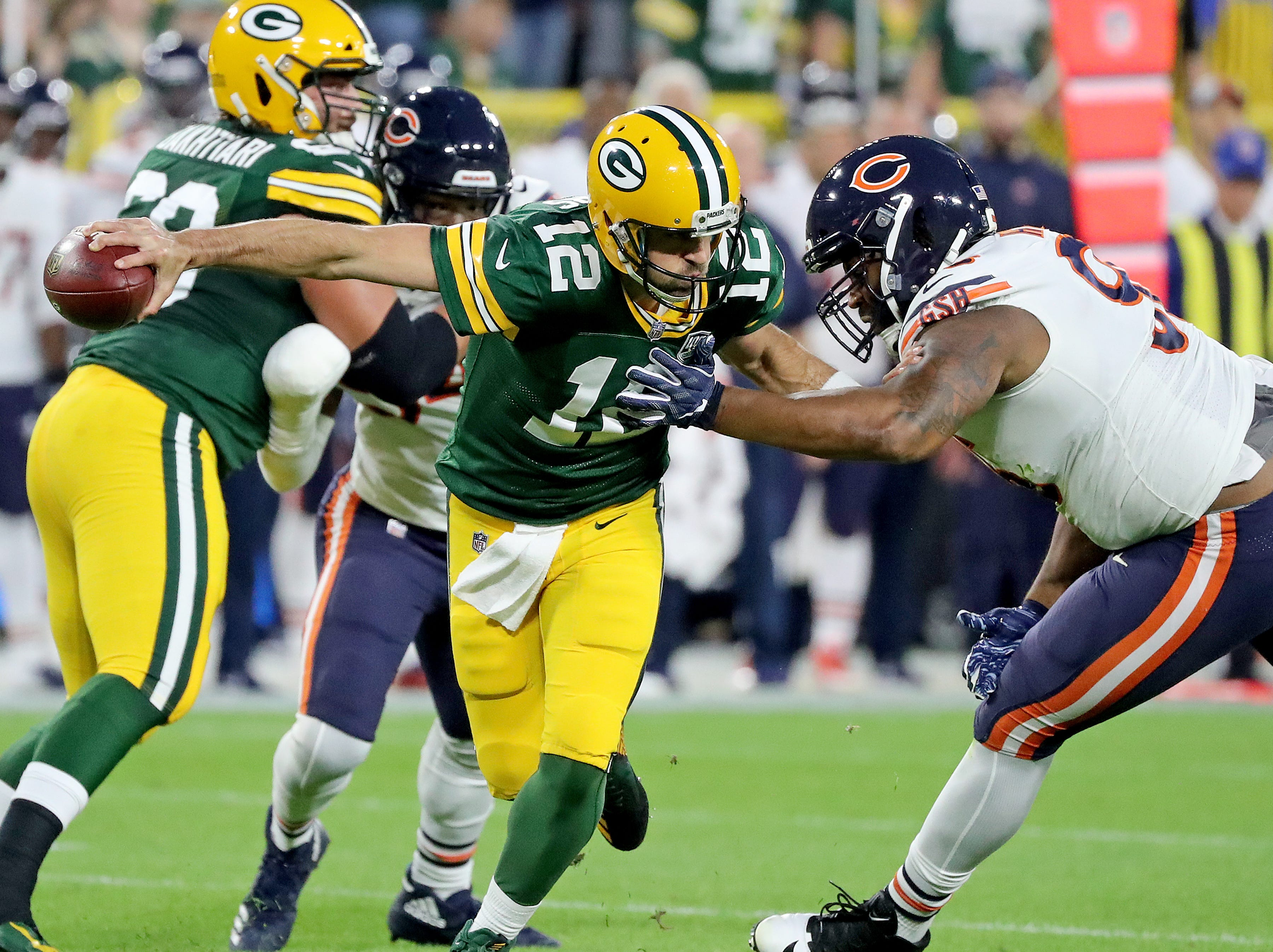 Green Bay Packers quarterback Aaron Rodgers (12) barely escapes the rush of defensive end Akiem Hicks (96) against the Chicago Bears Sunday, September 9, 2018 at Lambeau Field in Green Bay, Wis.