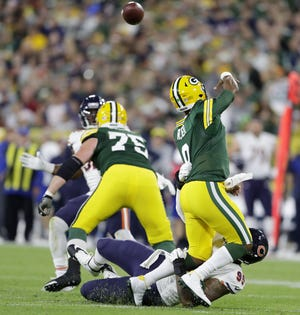 Green Bay Packers quarterback DeShone Kizer (9) is hit by Chicago Bears defensive end Roy Robertson-Harris (95) as he throws in the second quarter at Lambeau Field on Sunday, September 9, 2018 in Green Bay, Wis.