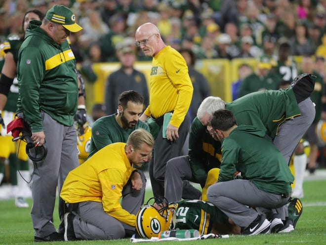 Green Bay Packers head coach Mike McCarthy (left) watches as quarterback Aaron Rodgers (12) is tended to by the training staff after being injured during the second quarter of their game against the Chicago Bears Sunday, September 9, 2018 at Lambeau Field in Green Bay, Wis.