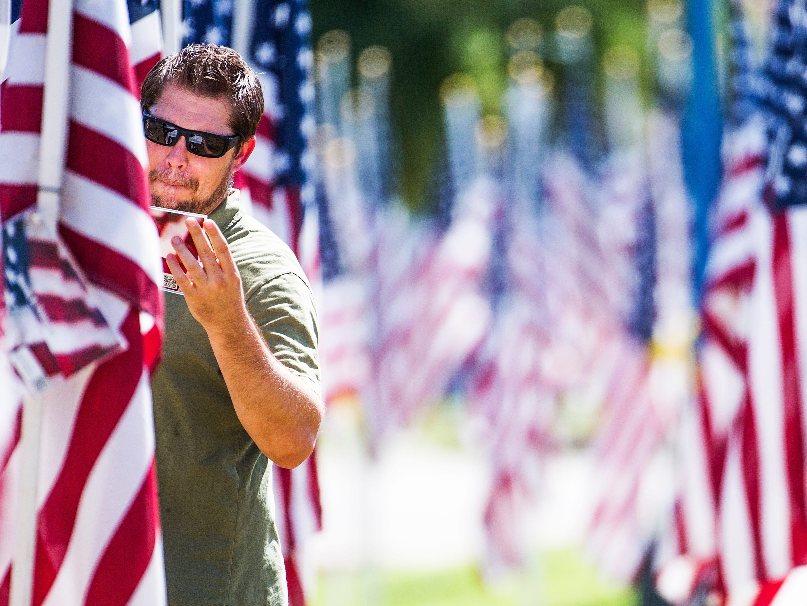 David Manzer, 43, Mesa, listens to a podcast about the Navy SEAL who killed Osama bin Laden as he reads the names of people killed during the 9-11 attacks. Manzer spent his lunch hour walking through the Healing Field, a memorial of almost 3,000 flags planted to honor those killed on Sept. 11, 2001.