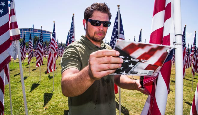 David Manzer, 43, Mesa, listens to a podcast about the Navy SEAL who killed Osama bin Laden as he reads the names of people killed during the 9/11 attacks.  Manzer spent his lunch hour walking through the Healing Field, a memorial of almost 3,000 flags planted to honor those killed on Sept. 11, 2001.