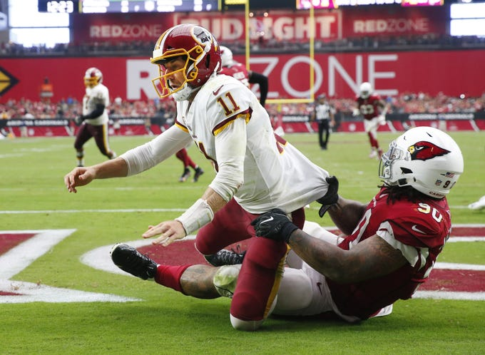 Arizona Cardinals defensive tackle Robert Nkemdiche (90) tackles Washington Redskins quarterback Alex Smith (11) after he grew a pass during the third quarter at State Farm Stadium in Glendale, Ariz. September 9. 2018.