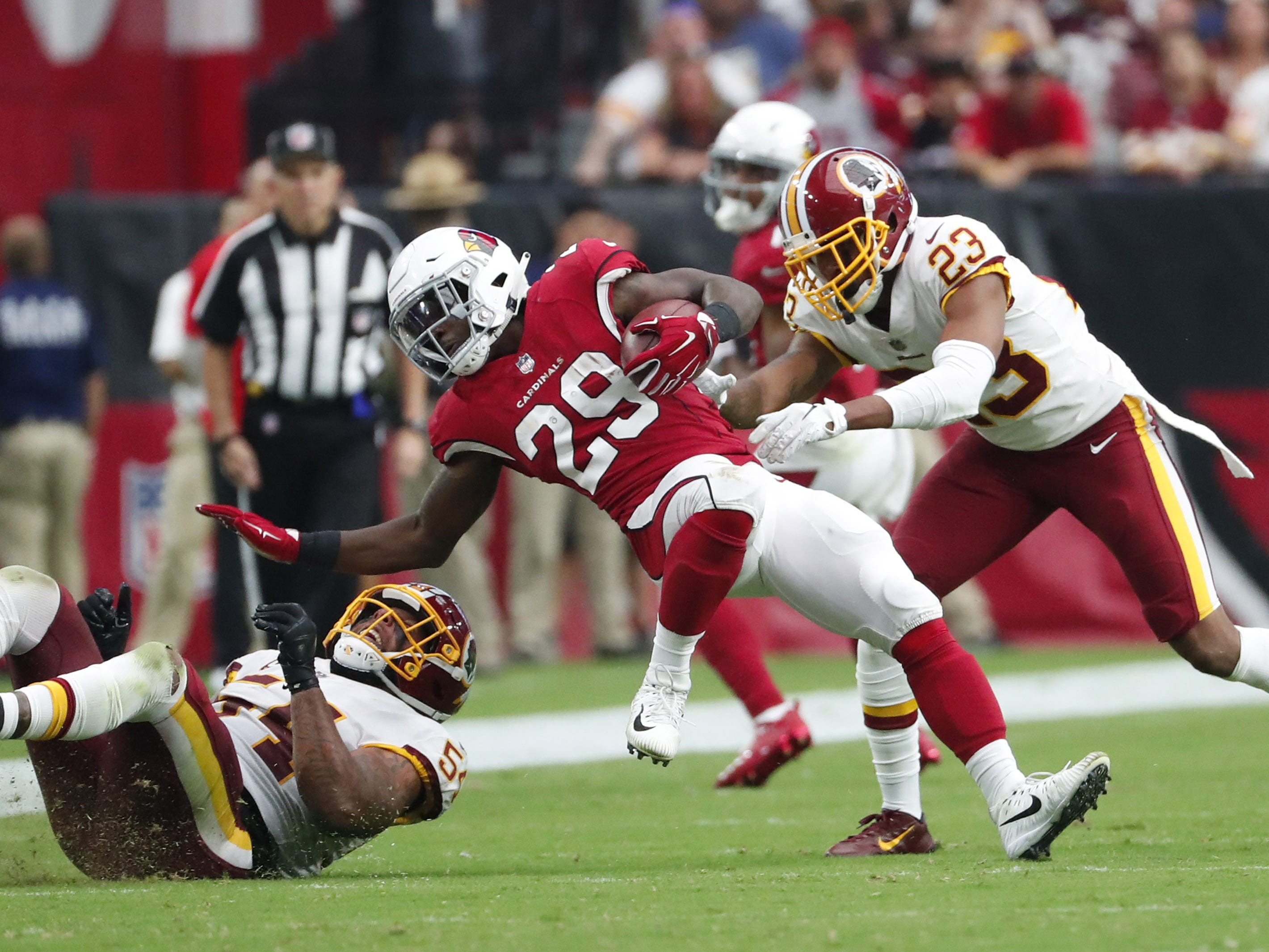 Arizona Cardinals running back Chase Edmonds (29) is tackled by Washington Redskins linebacker Mason Foster (54) and cornerback Quinton Dunbar (23) during the fourth quarter at State Farm Stadium in Glendale, Ariz. September 9. 2018.
