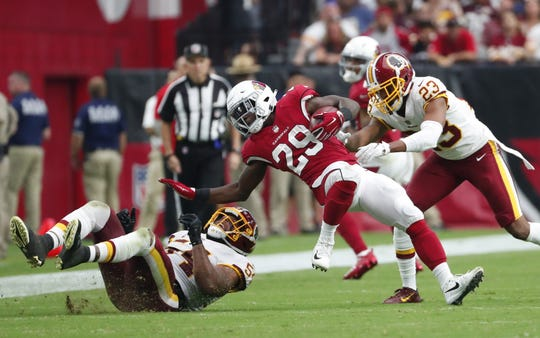 Cardinals running back Chase Edmonds (29) is tackled by Redskins linebacker Mason Foster (54) and cornerback Quinton Dunbar (23) on Sunday.
