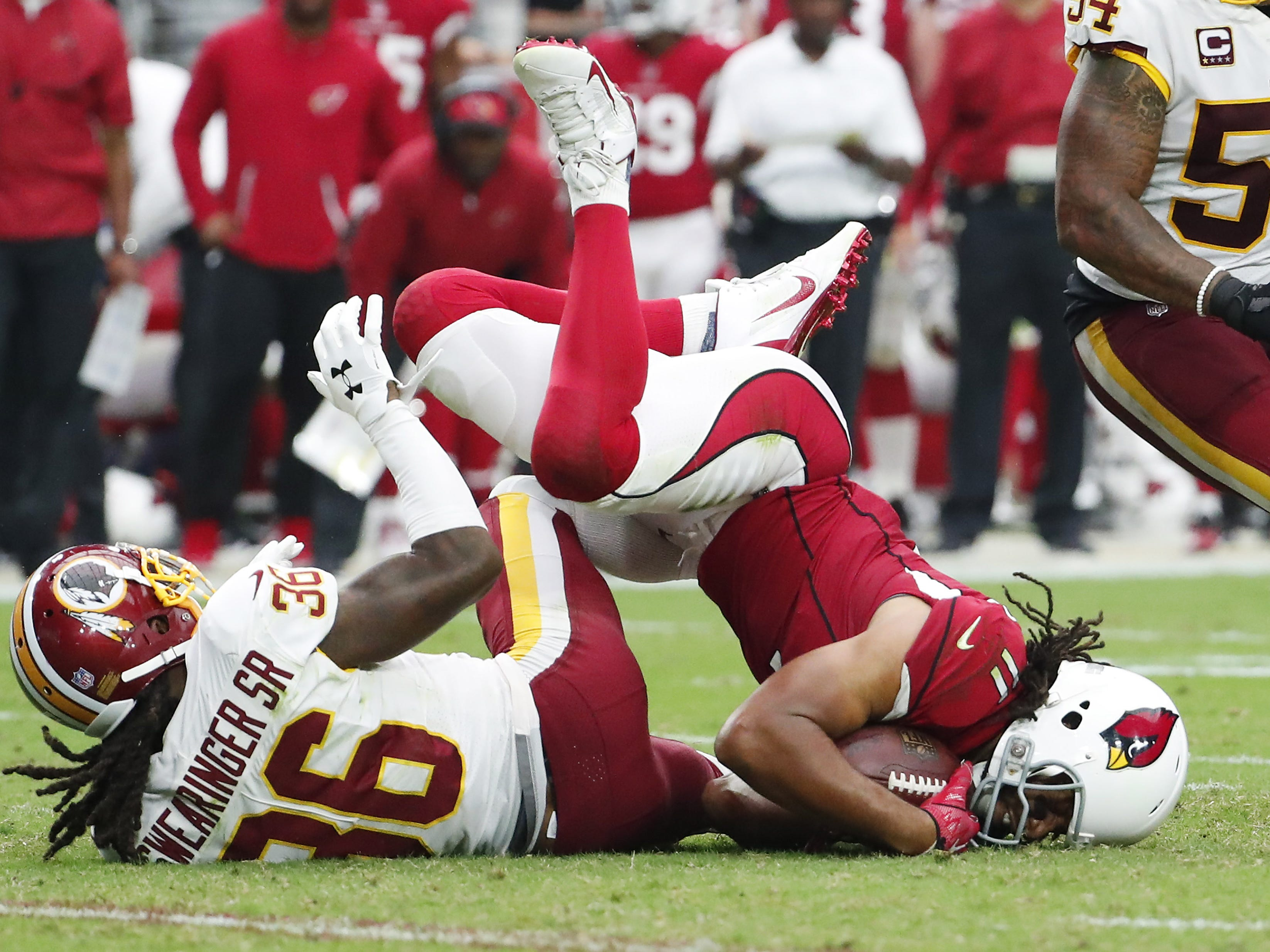 Arizona Cardinals wide receiver Larry Fitzgerald (11) is tackled by Washington Redskins defensive back D.J. Swearinger (36) after a catch during the third quarter at State Farm Stadium in Glendale, Ariz. September 9. 2018.