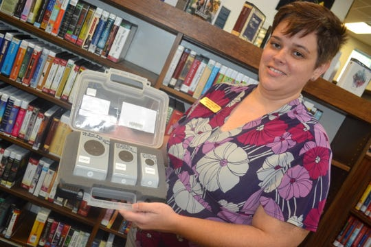 Ida Rupp Library director Lindsay Faust holds a box of punches that are part of the scrapbooking collection that patrons can borrow just like a book. Faust hopes to bring other nontraditional collections to the library as part of Ida Rupp's strategic plan.