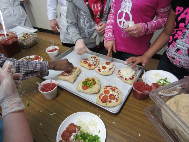 Students learn to make personal-sized pizzas at a cooking class held by Michigan State University Extension St. Clair County.