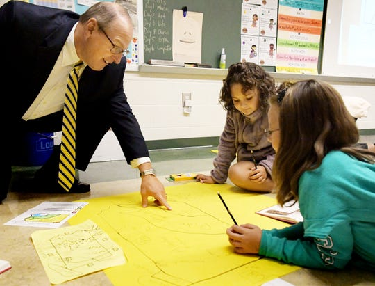 Eastern York School District's new superintendent, Joe Mancuso, looks at a mapping assignment with Wrightsville Elementary fourth-graders Myla Perez, left, and Morgan Enedy at the school Monday, Sept. 10, 2018. Bill Kalina photo