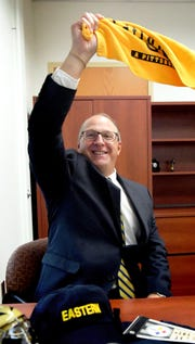 """A sports fan, Eastern York School District's new superintendent, Joe Mancuso, waves a Pittsburgh Steelers """"Terrible Towel"""" in his office while posing for a photo Monday, Sept. 10, 2018. Bill Kalina photo"""