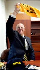 "A sports fan, Eastern York School District's new superintendent, Joe Mancuso, waves a Pittsburgh Steelers ""Terrible Towel"" in his office while posing for a photo Monday, Sept. 10, 2018. Bill Kalina photo"