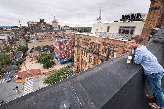 Dylan Bauer, director of development for RSDC, looks over Continental Square from the roof of the Rupp Building at 2 W. Market St. in York. Crews are renovating the building, which has sat on the southwest corner of the square, since 1893.