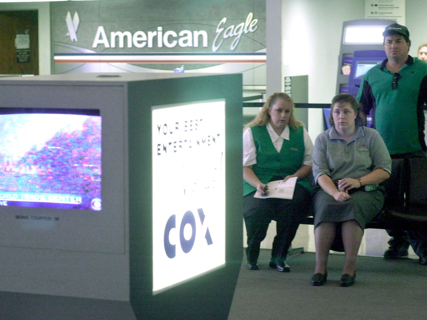 A group of workers watch live reports of the World Trade Center attacks on the news in the terminal of Mathis Field on Sept. 11, 2001.