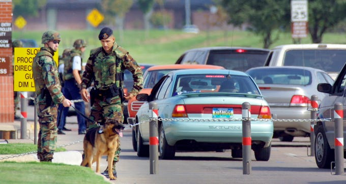 Guards in flack jackets and helmets check IDs at the south gate to Goodfellow Air Force Base on Sept. 11, 2001. The north gate was completely closed after the terrorist attacks on the World Trade Center and the Pentagon.