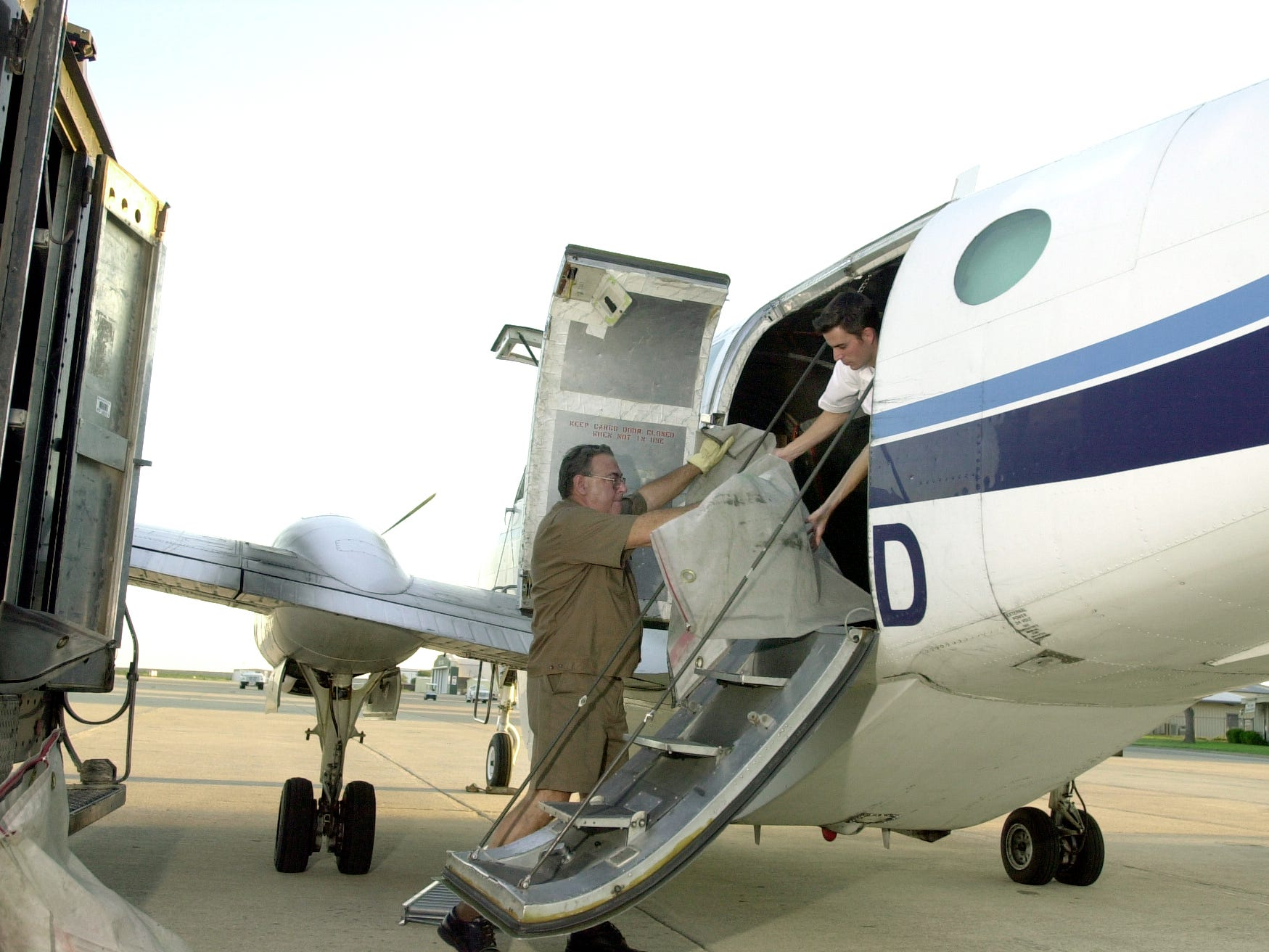 UPS employee Norman Trent (left) and Ameriflight Pilot Cory Pettit load the cargo bay of a plane Sept. 13, 2001, at Mathis Field. It was the companies' first shipment to leave San Angelo by air since the Sept. 11 grounding of all planes.