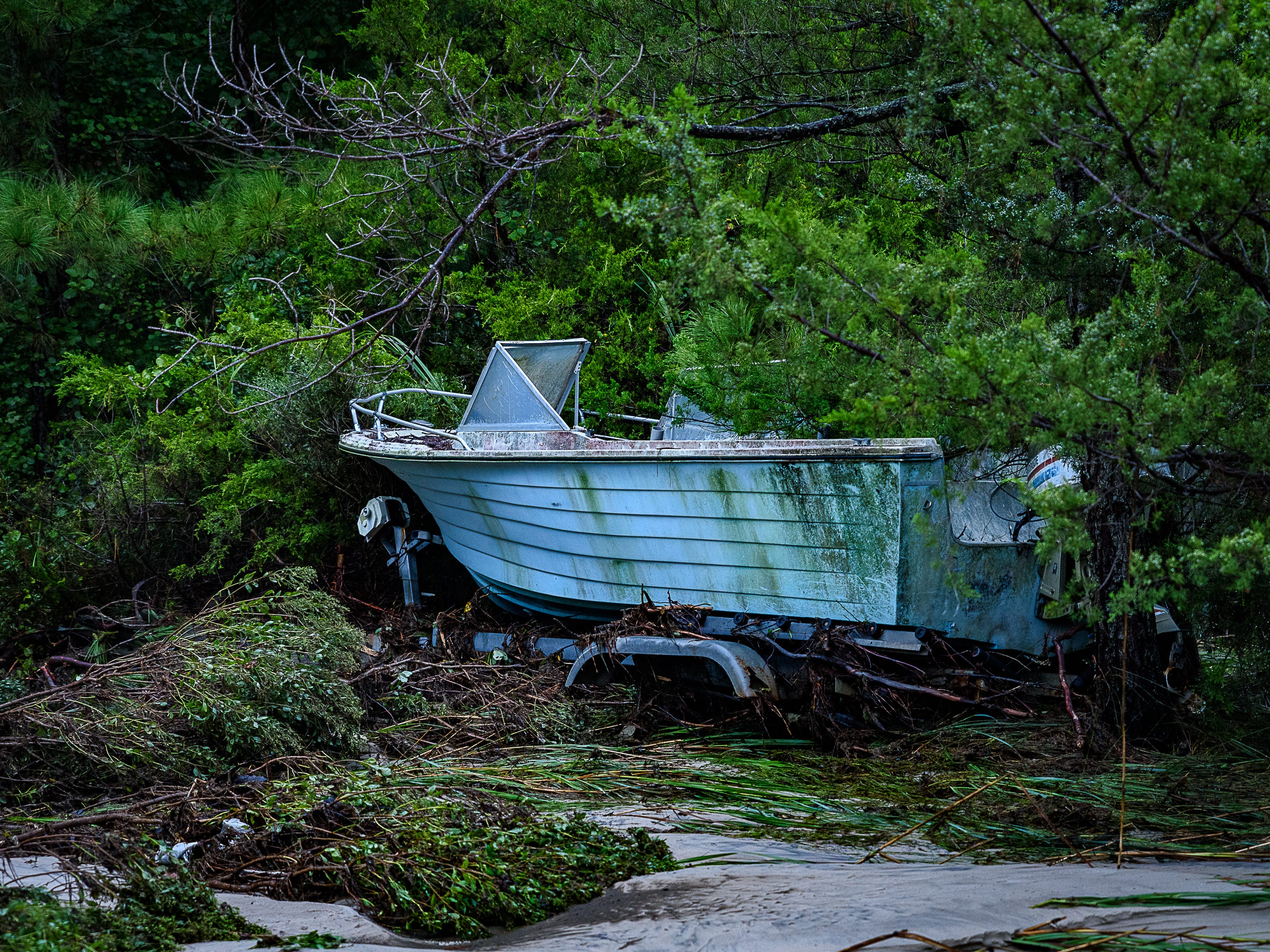A boat sits near the washed out road leading to this road leading  into the Hillsborough neighborhood in Belle Haven.