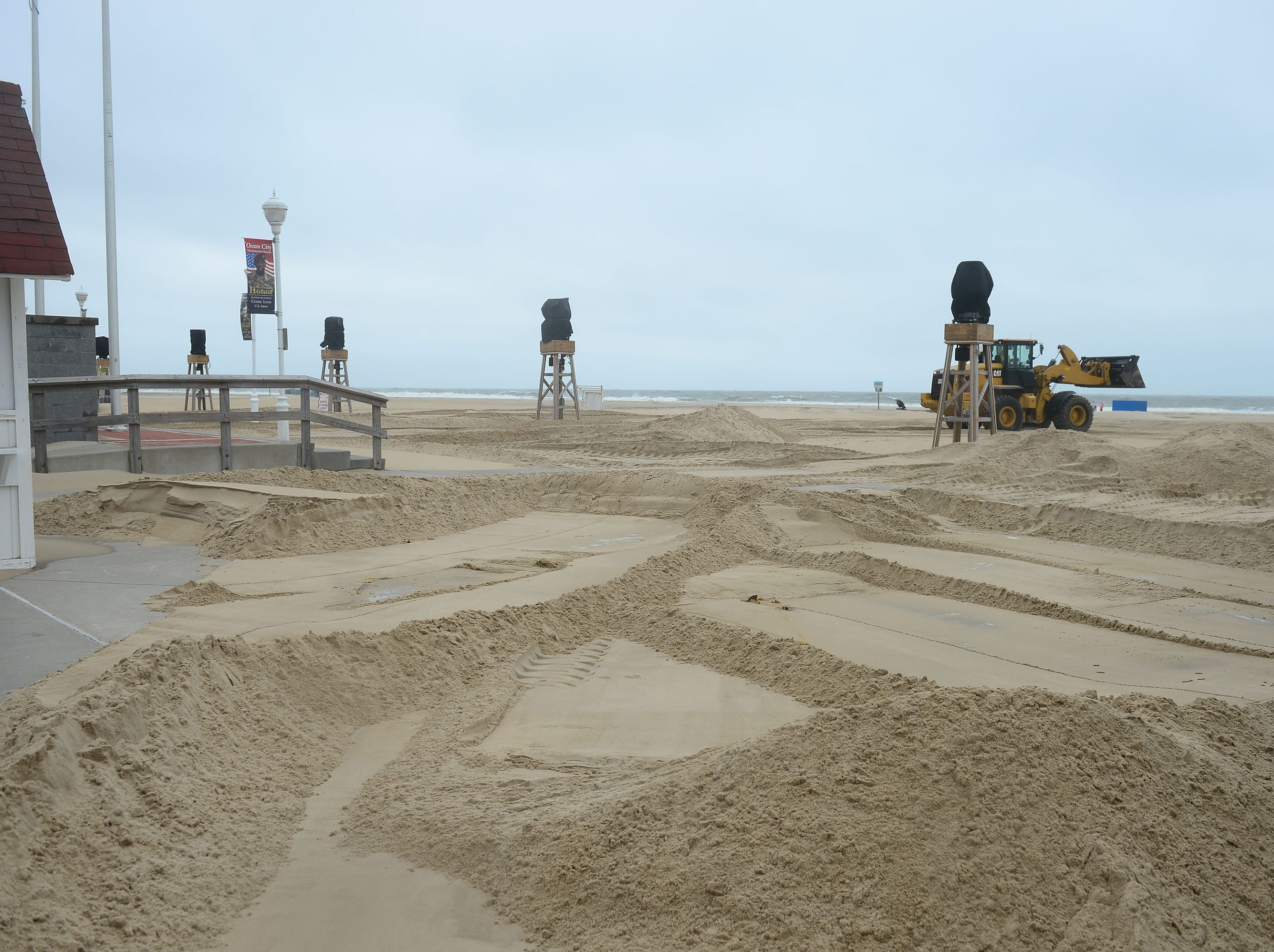 Ocean City works attempt to clear a large amount of sand that has been blown onto the boardwalk and tram routes on Monday, Sept. 10, 2018.