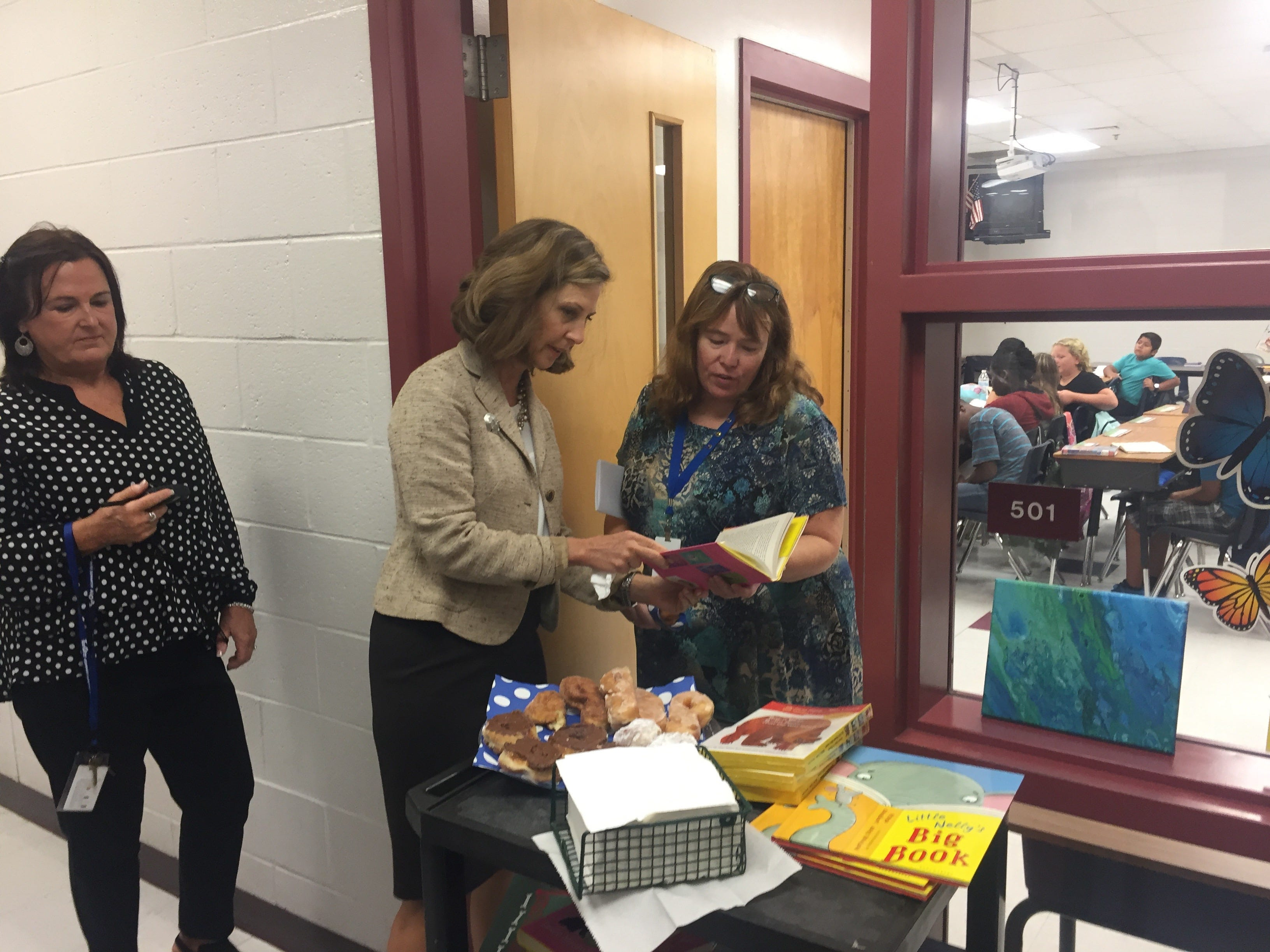 Virginia First Lady Pamela Northam shows a book to teacher Diana Kio during a visit at Accawmacke Elementary School in Daugherty, Virginia on Monday, Sept. 20, 2018.