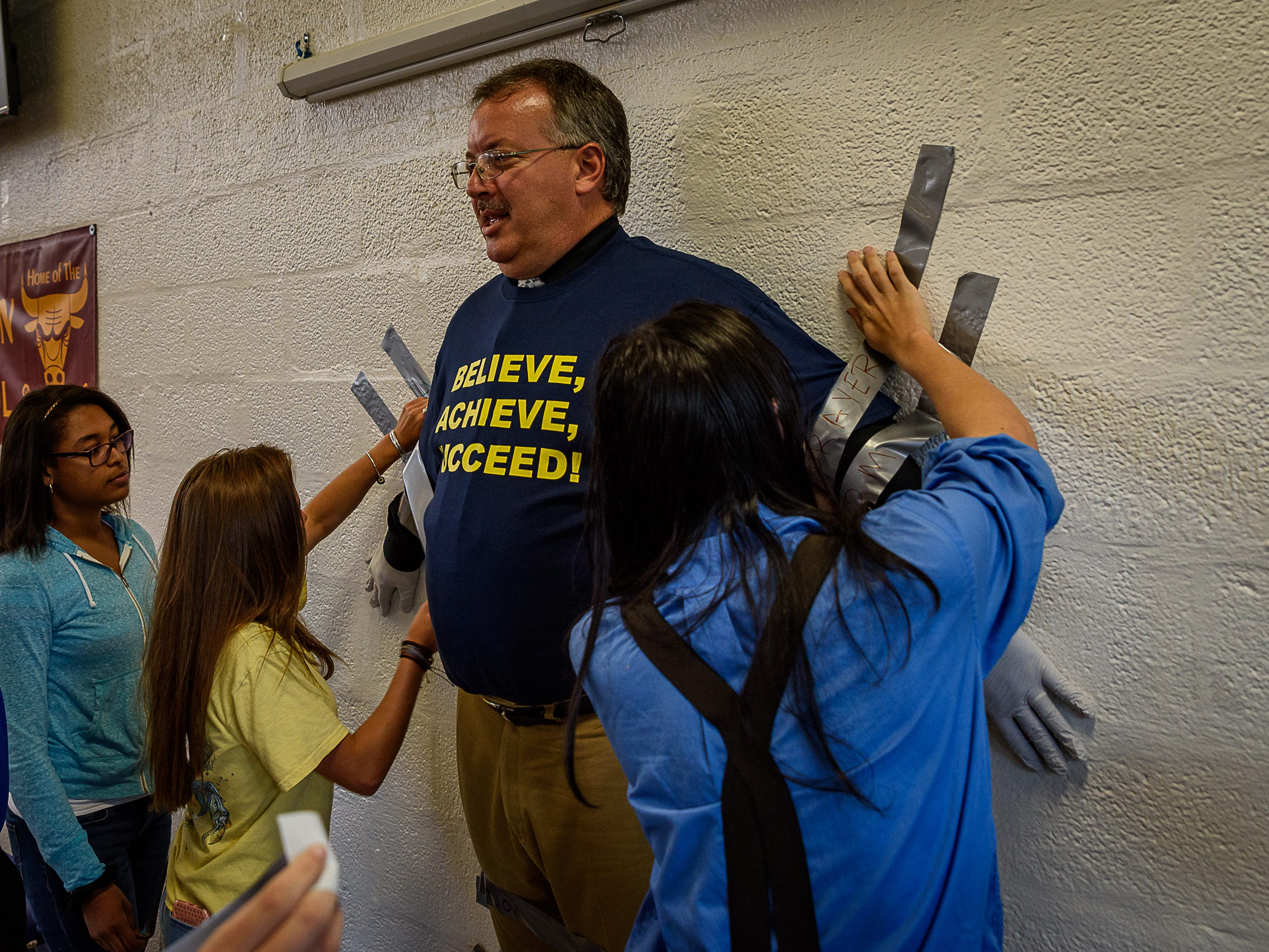 More students start to secure Principal Mike Myers to the wall.