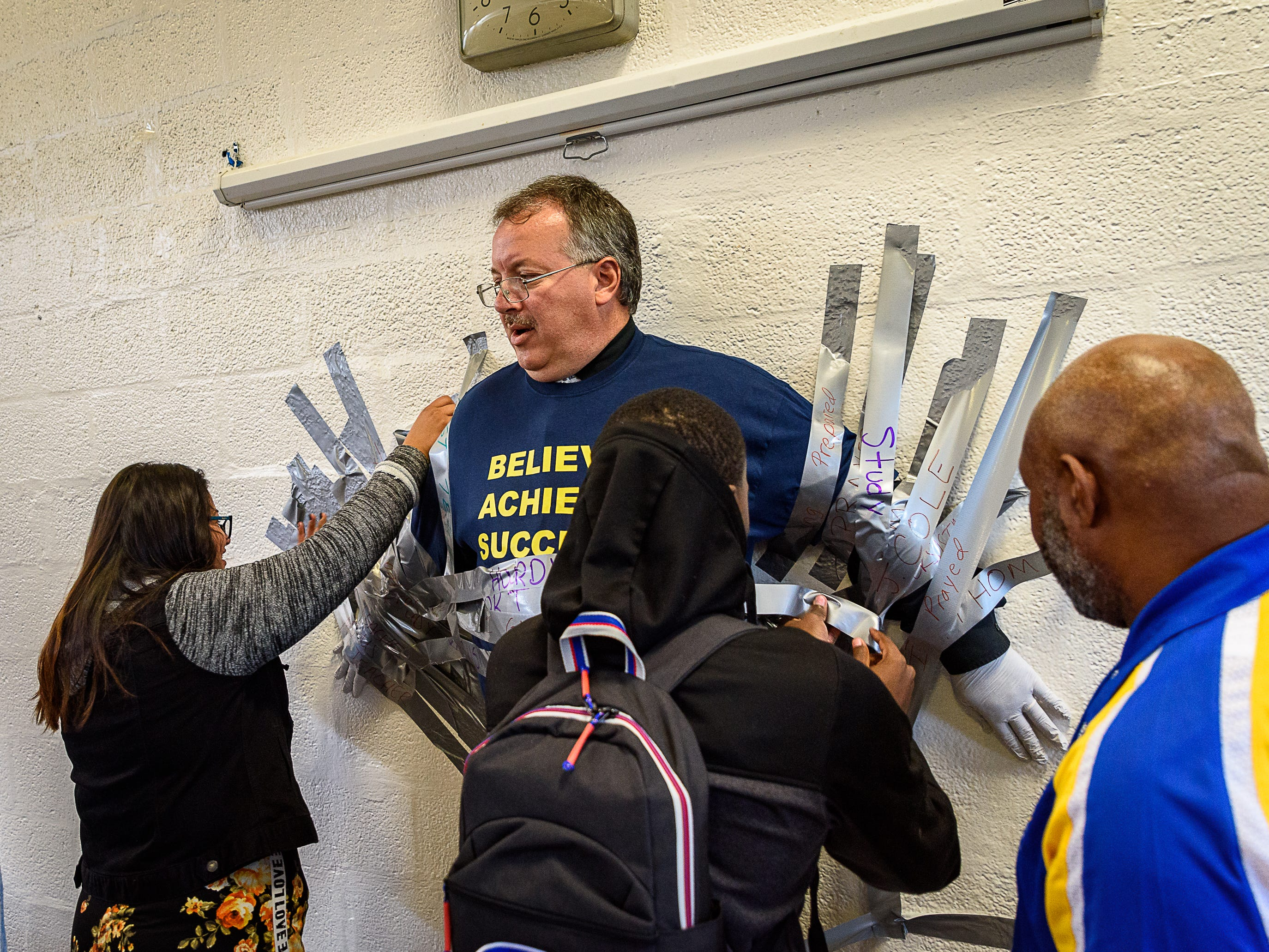 Students work to tape Principal Mike Myers to the wall at Northampton High School.