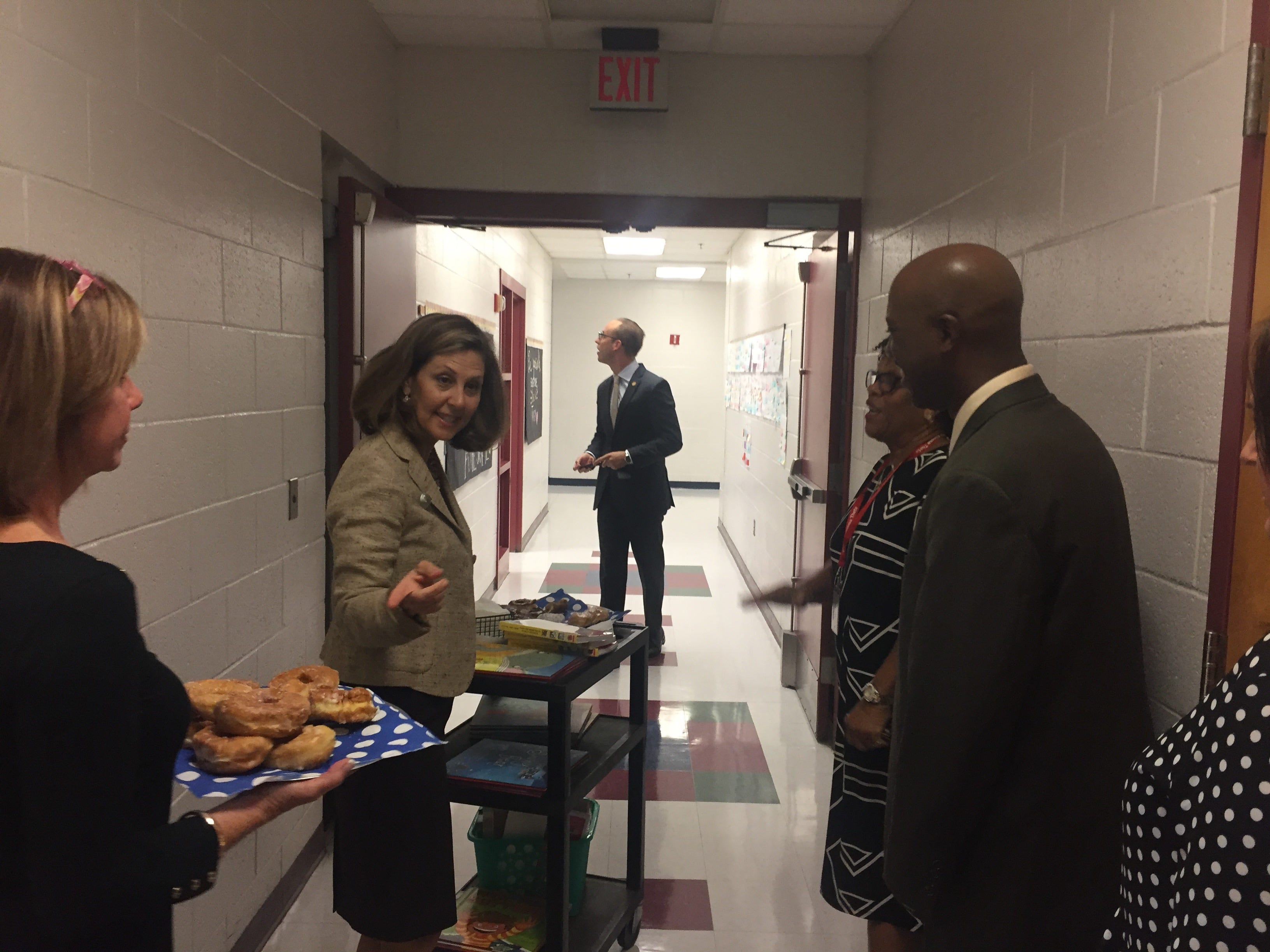Virginia First Lady wheels a cart carrying books, school supplies and donuts down the hallway at Accawmacke Elementary School in Daugherty, Virginia on Monday, Sept. 20, 2018. Northam visited the school as part of a statewide back-to-school tour to thank teachers and discuss the importance of school readiness.