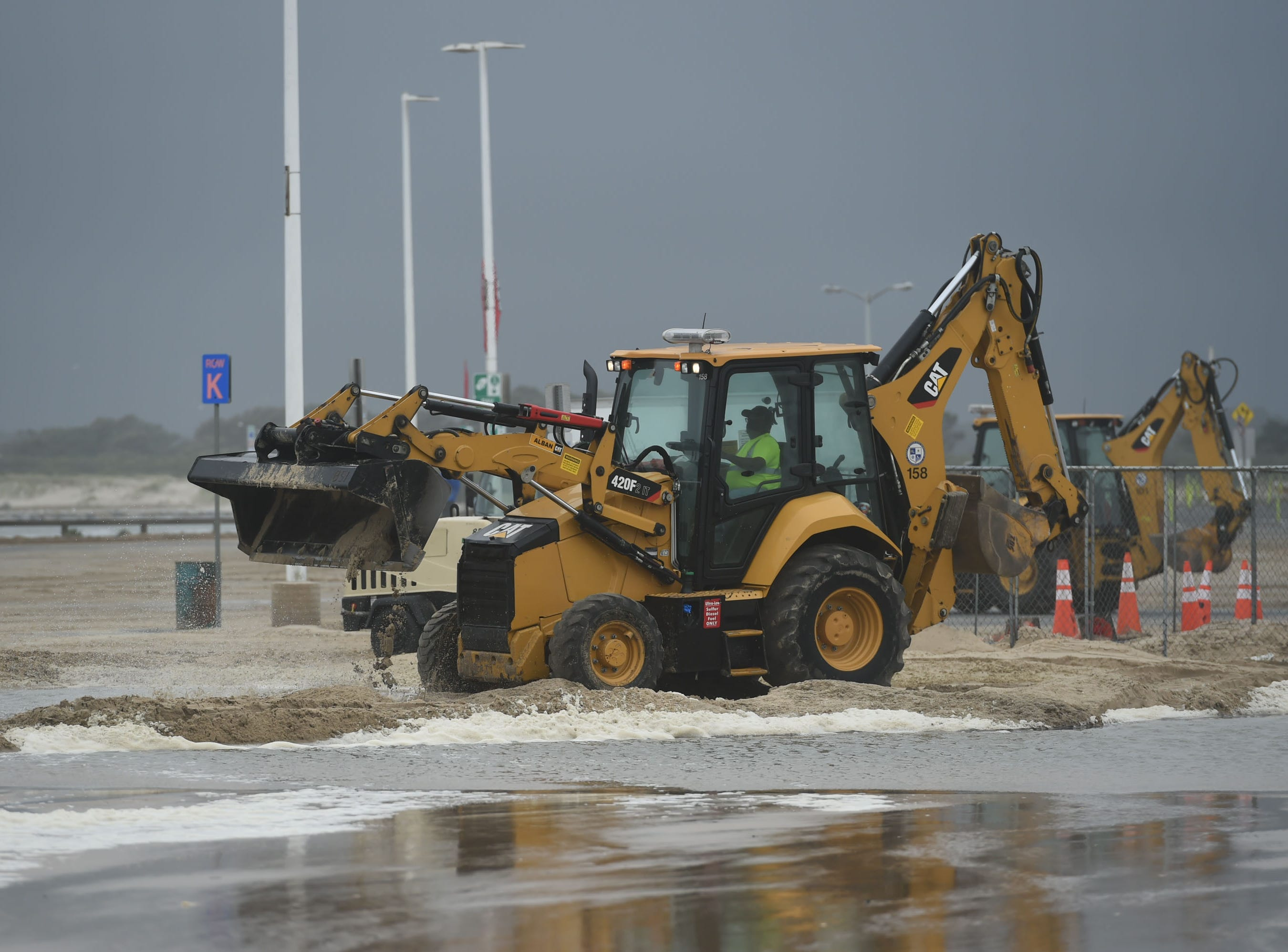 Ocean City workers attempt to clear sand from the Inlet parking lot on Monday, Sept. 10, 2018.