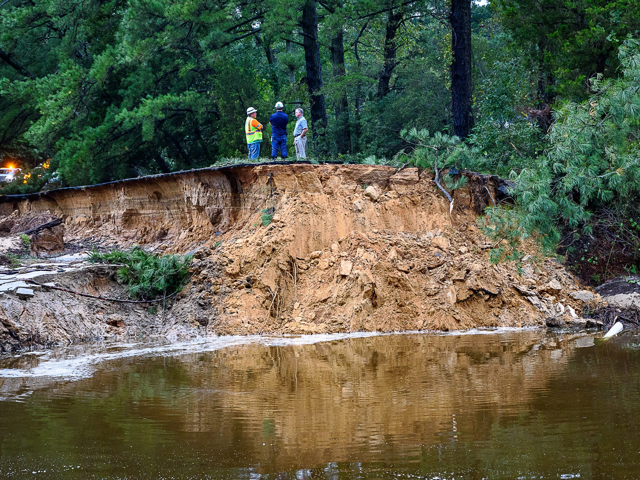 Virginia DOT officials look at the road Monday that was washed out by heavy rains in Belle Haven, Virginia.