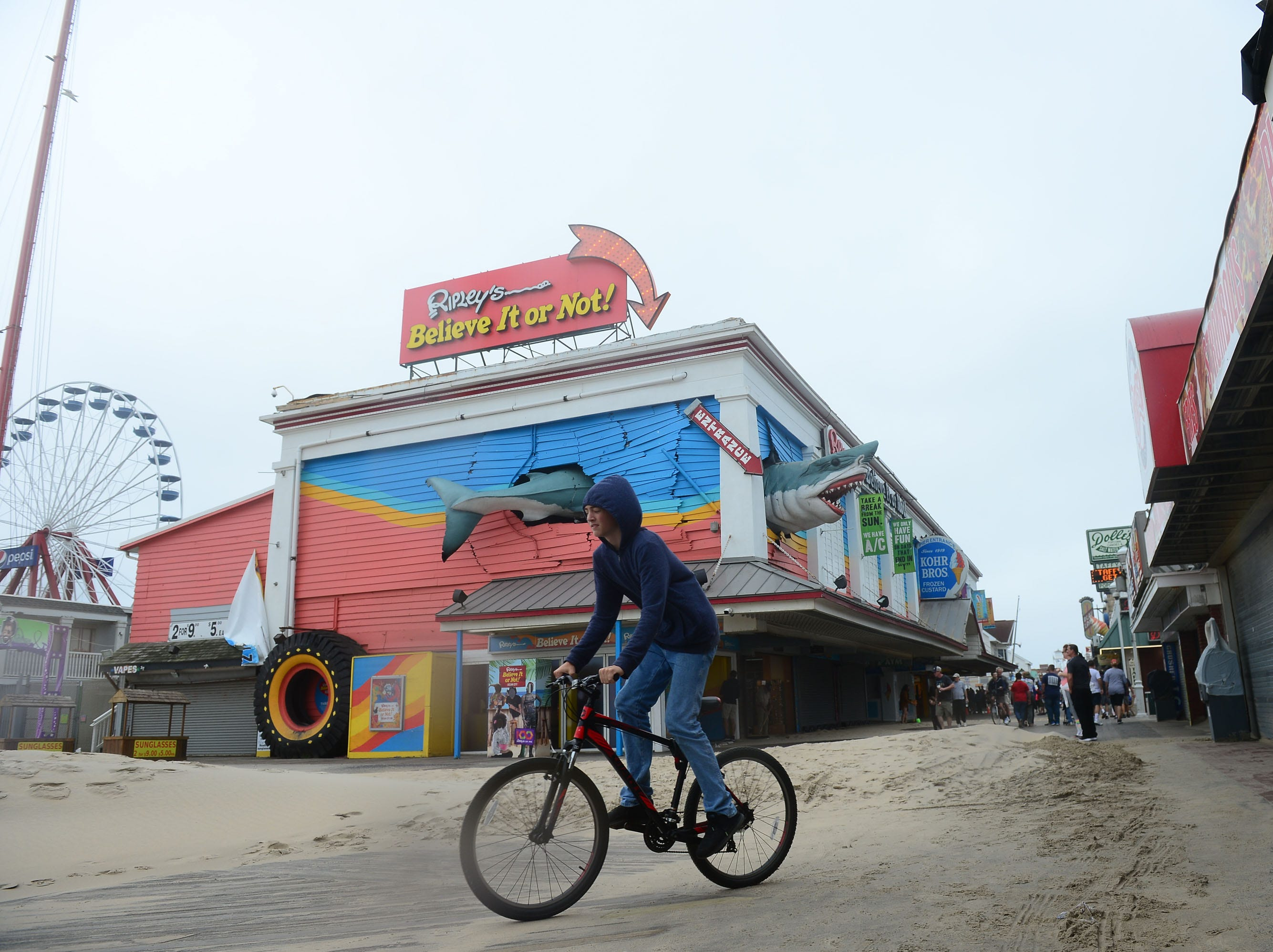 A biker rides his bike down the boardwalk over large amounts of sand on Monday, Sept. 10, 2018 in Ocean City, Md.