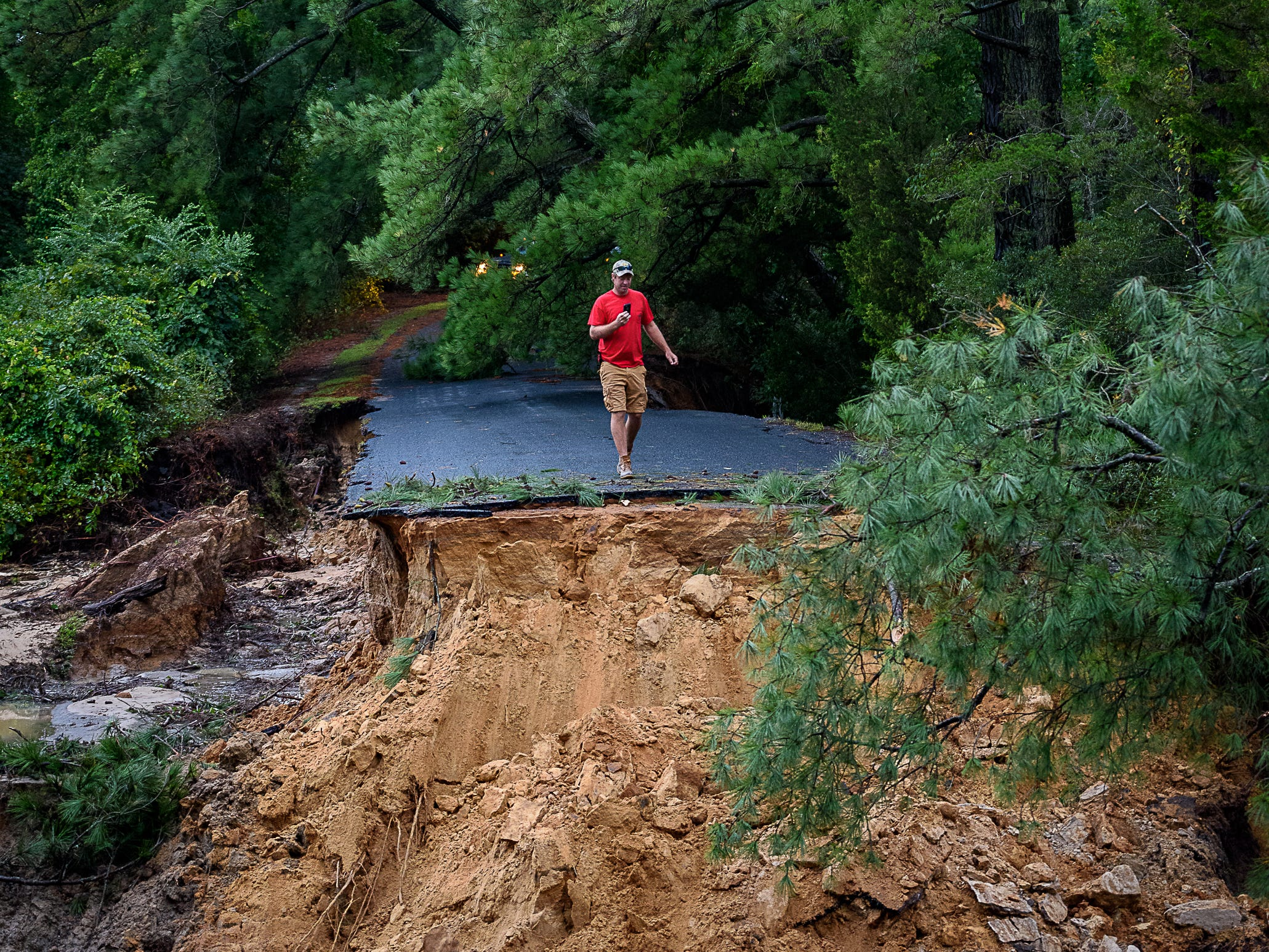 A resident takes a photo of the damage caused by flooding to this road in Belle Haven.