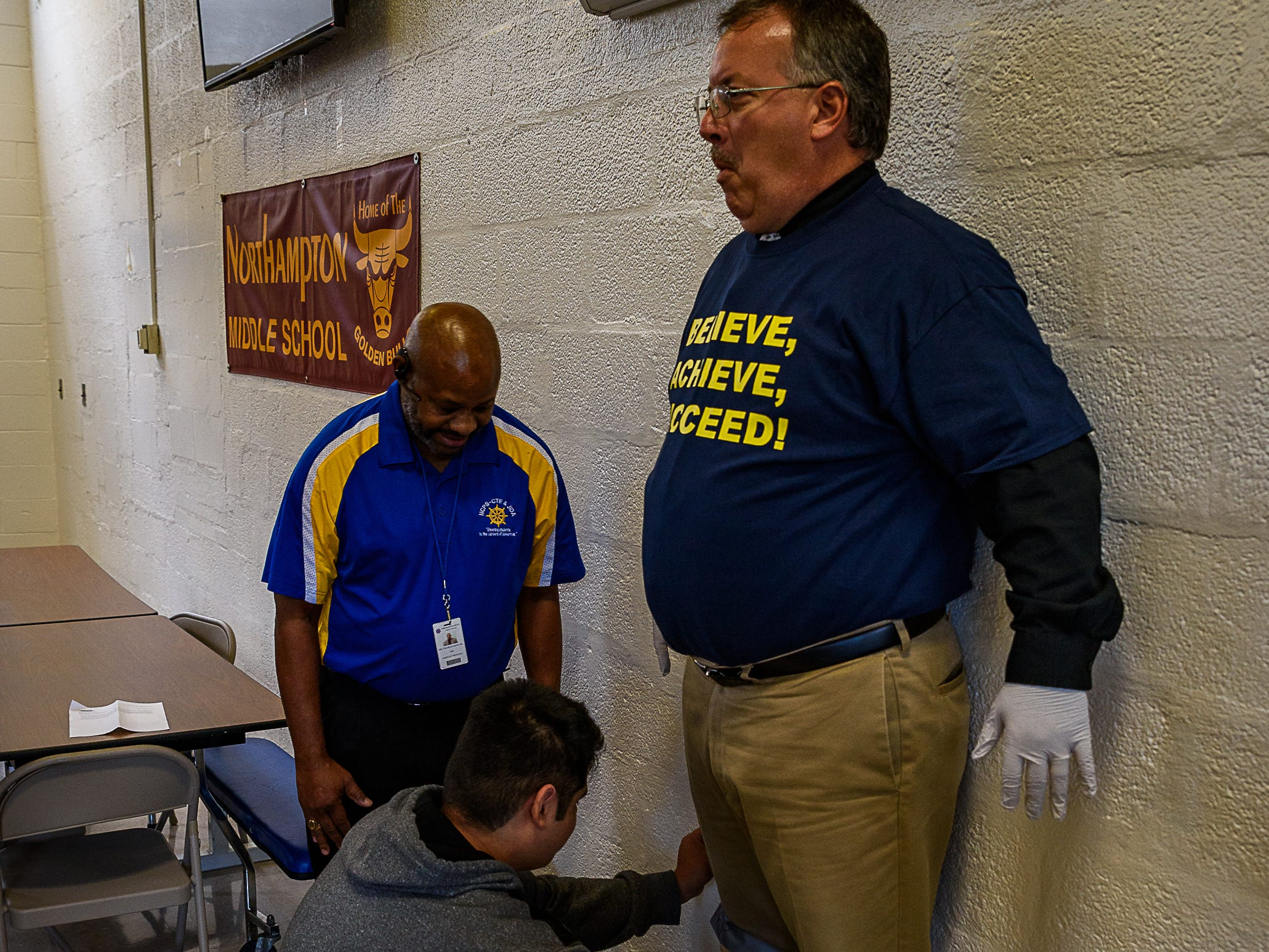 With some help from Assistant Principal Charles King, the first student starts the process of taping Principal Mike Myers to a wall at Northampton High School.