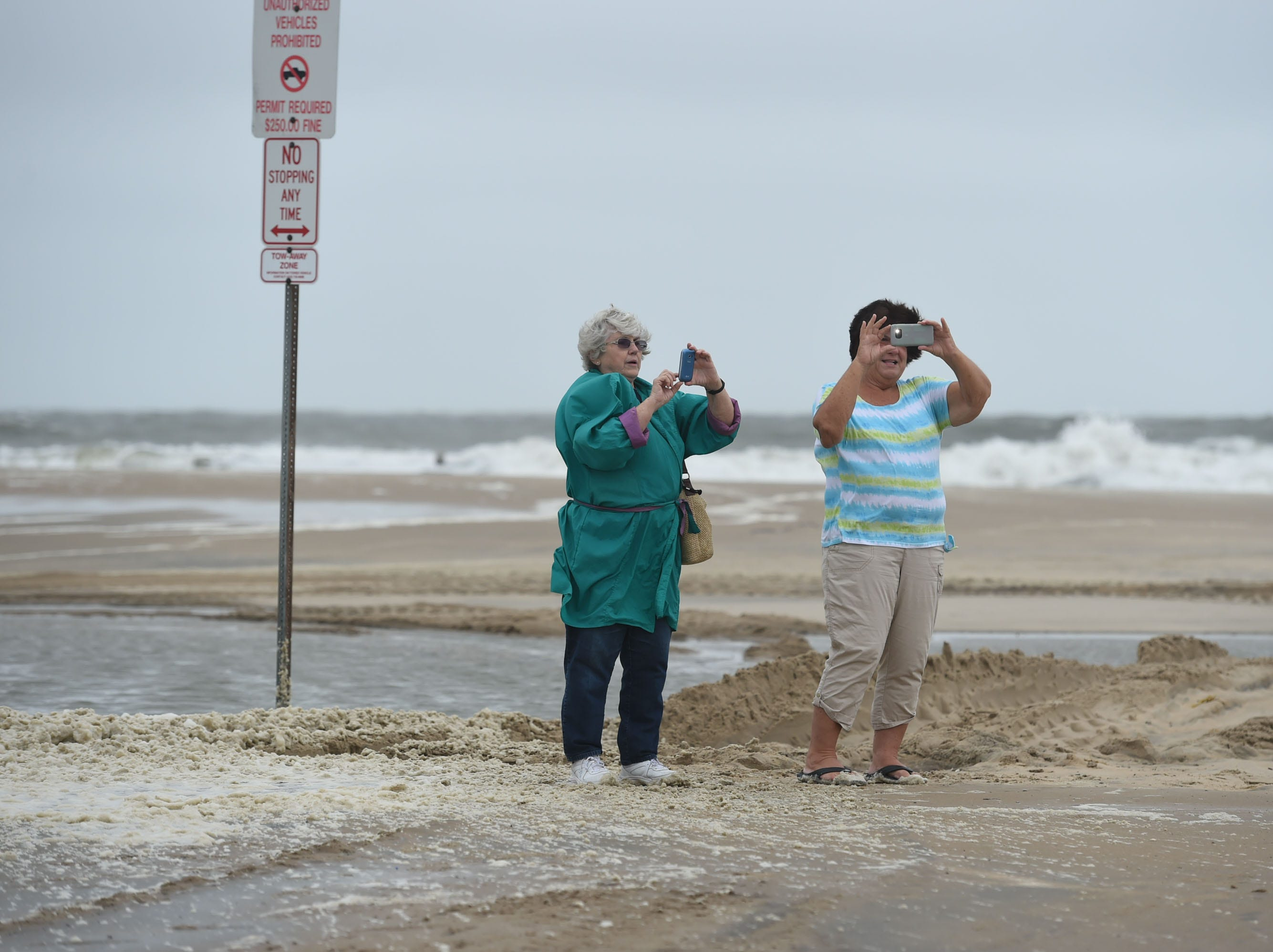 People flock to the inlet to take photos of high seas and large waves on Monday, Sept. 10, 2018.