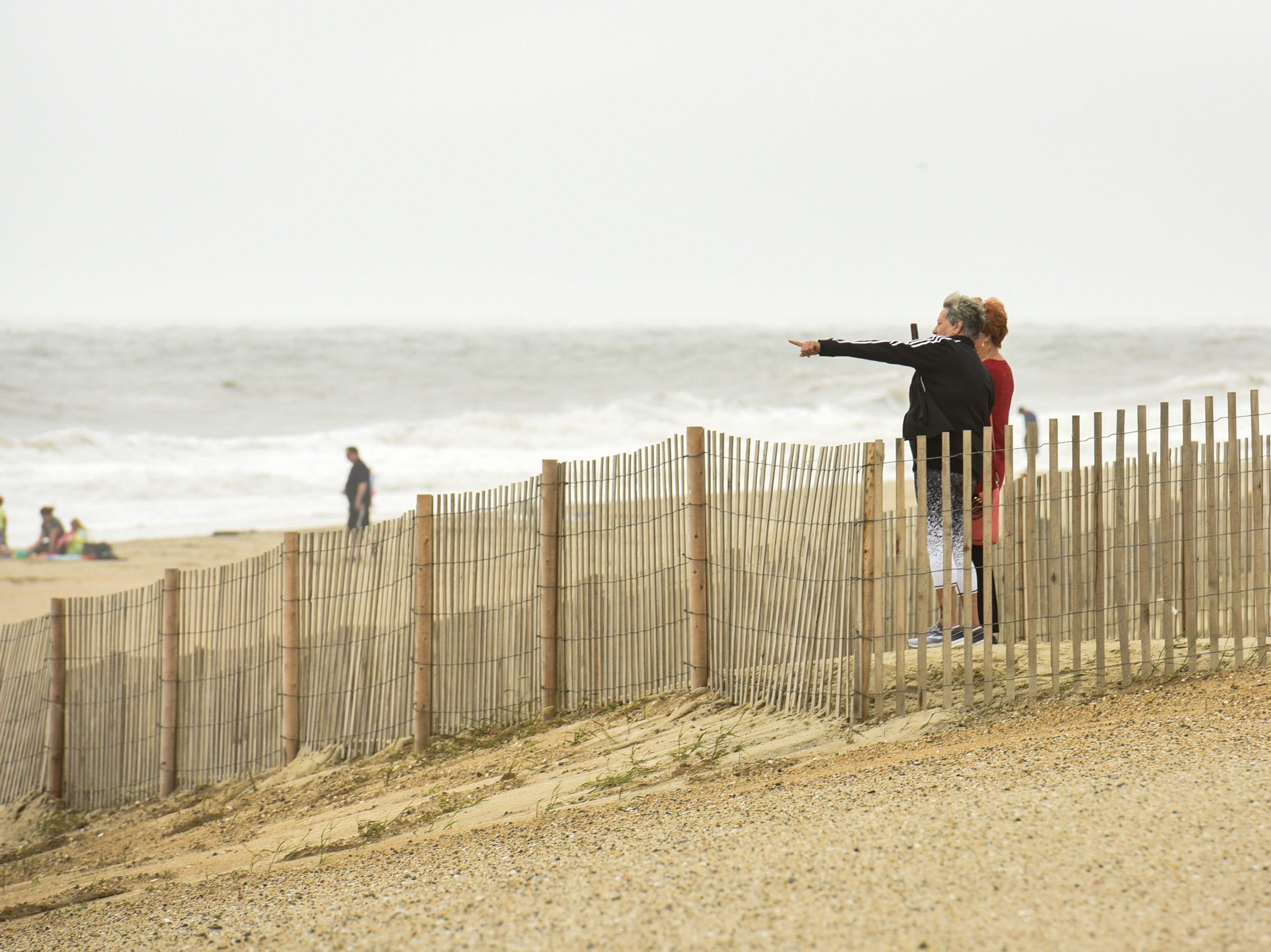 Beach goers watch the ocean on a windy day in Bethany Beach, Monday Sept. 10.