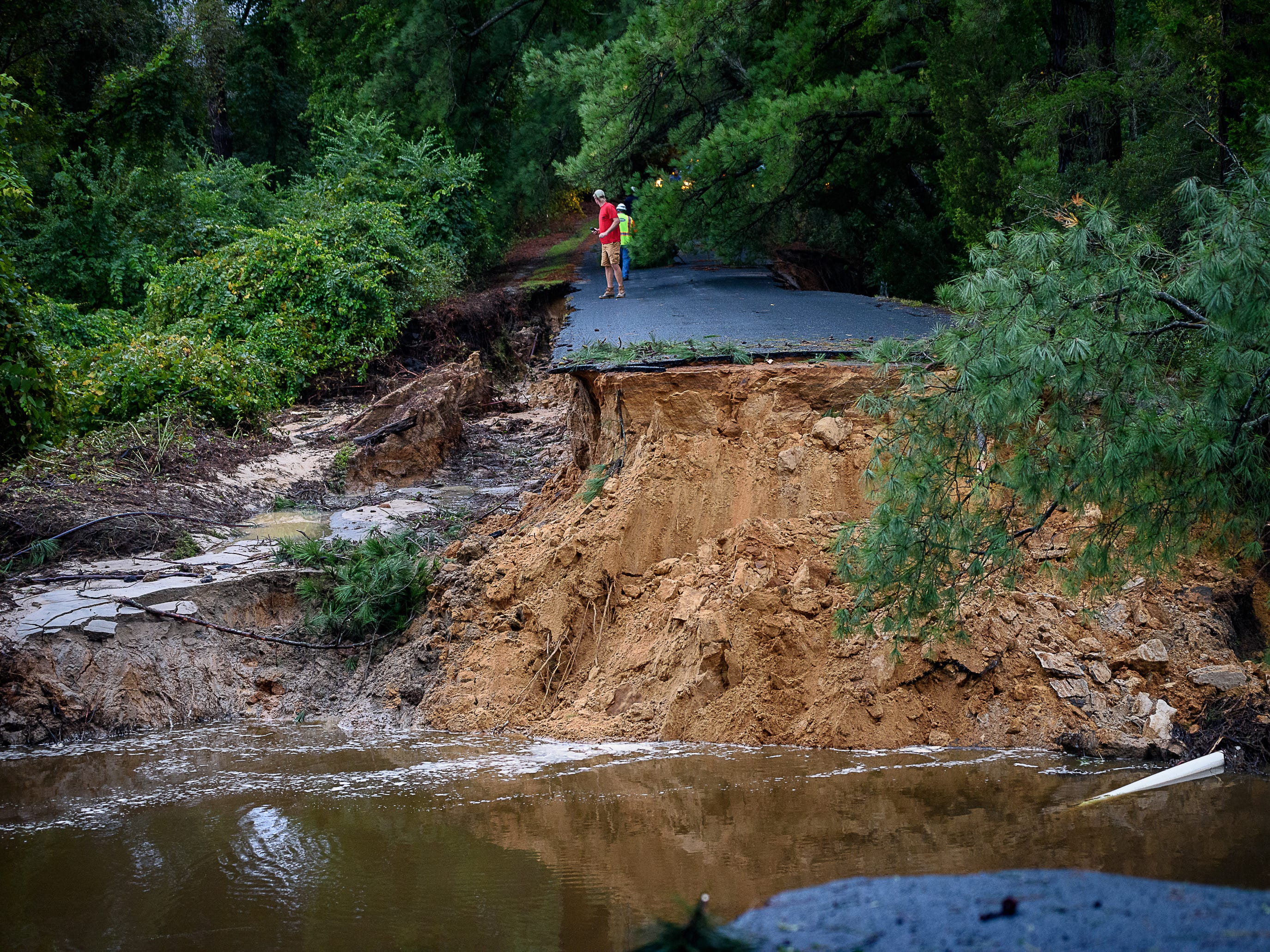 Two residents look at the washed out road leading to the  Hillsborough neighborhood in Belle Haven on Monday morning, Sept. 10.