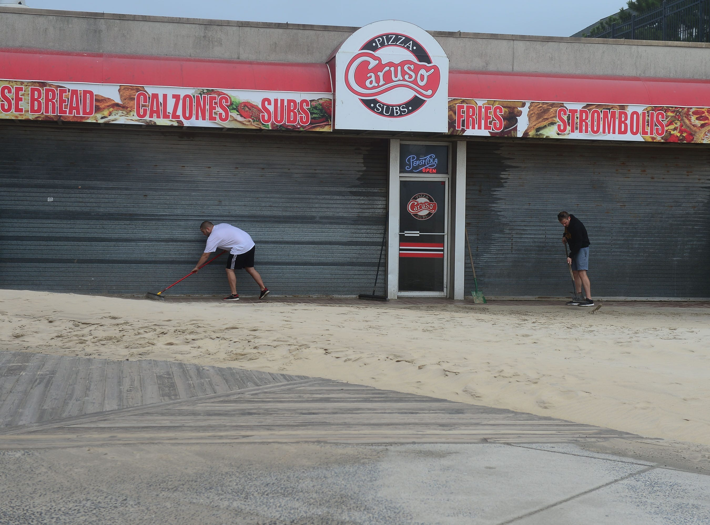 Business owners try to shovel sand away from their doors in Ocean City, Md. on Monday, Sept. 10, 2018.