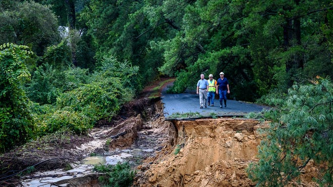 Virginia Department of Transportation officials check out the road washed out by flooding on Monday, Sept. 10. It is the only road leading to the only road leading into the Hillsborough neighborhood in Belle Haven.