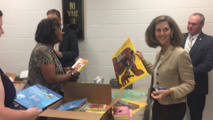 Virginia First Lady Pamela Northam, right, helps Reading Specialists Amanda Marshall and Sherry Kinsey unpack books and school supplies during a visit to Accawmacke Elementary School in Daugherty, Virginia on Monday, Sept. 20, 2018.