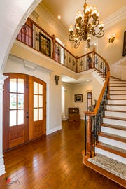 A sweeping staircase and soaring ceiling greets guests upon entry into the home.