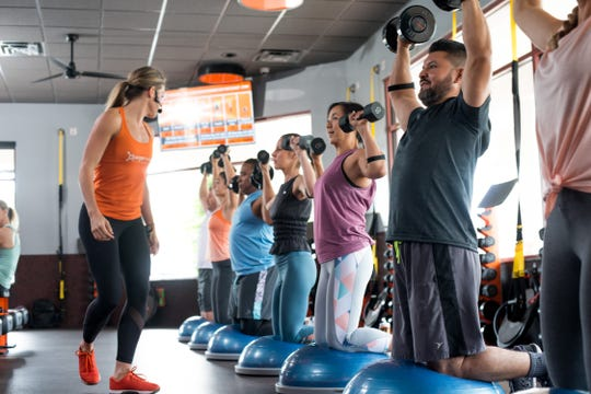 This publicity image produced and distributed by Orangetheory shows one workout session.