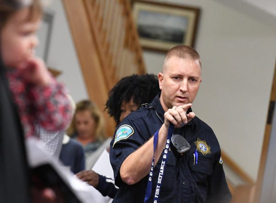 A fire department official counts the crowd to make sure the meeting room did not exceed its 110 capacity.
