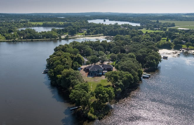 """Known as """"The Castle House,"""" this island haven on Cedar Island Lake in Richmond has been a much sought-after property."""