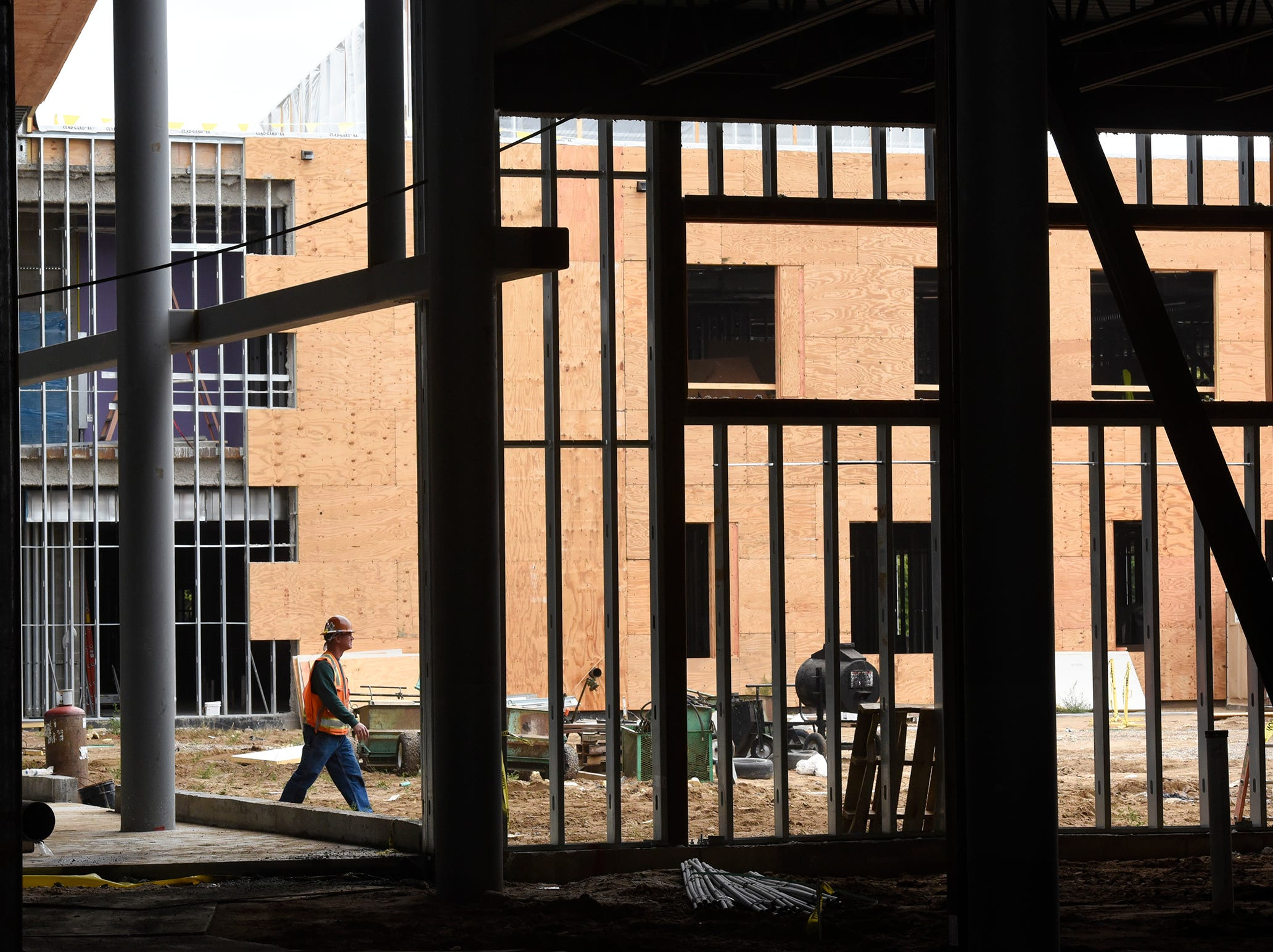 Workers walk between beams near the commons area Monday, Sept. 10, at the new Tech High School site in St. Cloud. Now a year into the building project, about 150 workers are on site daily and the focus has turned to inside the $104.5 million structure. See Page 3A for the latest progress.