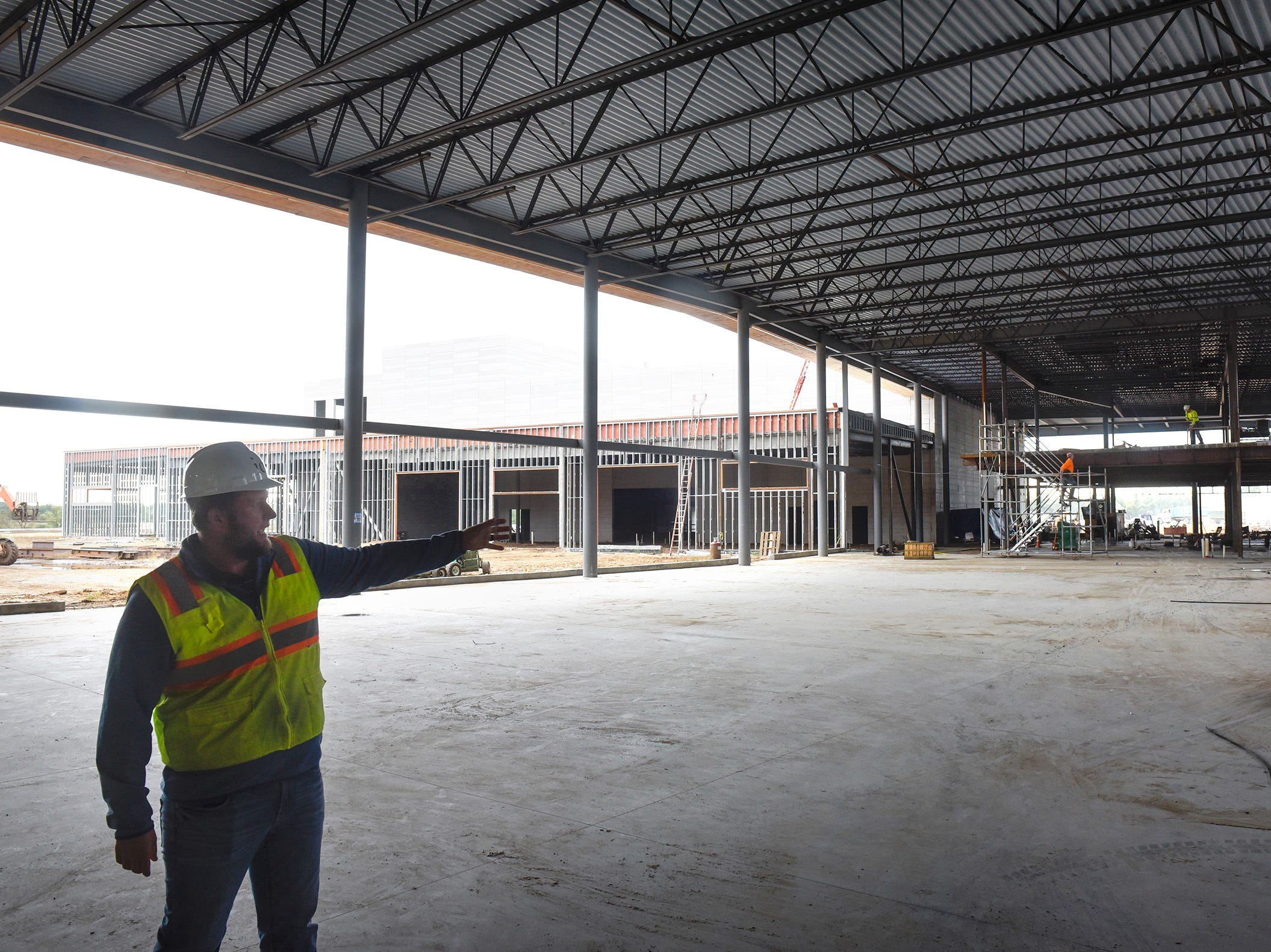 Site manager Kyle Walter talks about features under construction in the future commons area Monday, Sept. 10, at the new Tech High School building in St. Cloud.
