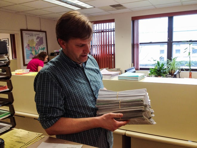Stevens Point City Clerk John Moe holds a stack of new voter registrations at City Hall.