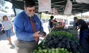 STAR FILE PHOTO Ed Williams, Ventura County's agricultural commissioner, examines avocados at a farmer's market in Thousand Oaks in 2018.