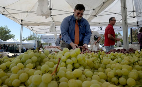 Ed Williams, agricultural commissioner for Ventura County, checks out some grapes from Lee Family Farms at the Thousand Oaks Farmer's Market.