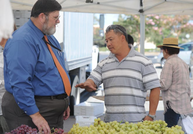 Ed Williams, (left) agricultural commissioner for the Ventura County, talks with Ken Lee, owner of Lee Family Farms at the Thousand Oaks Farmer's Market. Lee sells grapes and different kinds of peaches.